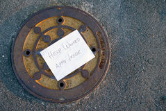 Help Wanted. A Help Wanted sign on top of a manhole cover Royalty Free Stock Photography