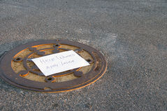Help Wanted. A Help Wanted notice on a sewer manhole cover Royalty Free Stock Photo