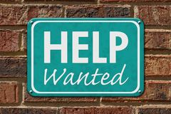 Help Wanted Sign on a brick building. Help Wanted  Sign, A teal sign with text Help Wanted  on a brick building Royalty Free Stock Image