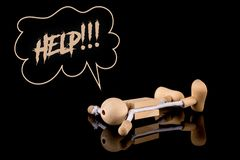 Help, Wooden Stick Figure fallen on the ground the word Help on black background. Reflective surface royalty free stock image