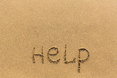 Help - word drawn on the sand beach. Abstract. Royalty Free Stock Photo