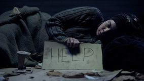 Help word on poster holding poor homeless beggar lying on dirty street, charity. Stock photo stock photo