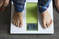 Help word on weight scale display with child's feet standing in front of his mother royalty free stock image
