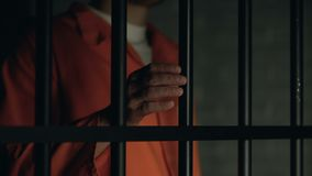 Help word written on prisoner fingers, male holding jail bars, ill treatment. Stock footage stock video