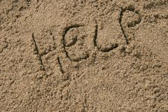 Help written in sand Stock Photography