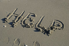 HELP written in sand. HELP inscription on a sand beach Royalty Free Stock Image
