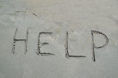Help written in the sand Stock Images