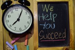 We Help You Succeed on phrase colorful handwritten on chalkboard. And alarm clock with motivation, inspiration and education concepts. Table background stock photos