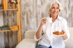 Help yourself with drink and croissant Stock Photography