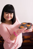 Help yourself, please!. Copy-spaced portrait of a young pastry chef with delicious muffins posing at camera Royalty Free Stock Photography