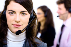 Helpdesk. Customer service team working in headsets, smiling. Woman in front Royalty Free Stock Images