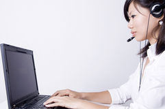 Helpdesk. Female Asian consultant with headsets working on laptop computer Royalty Free Stock Photos
