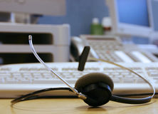 Helpdesk Headset. A telephone headset with helpdesk equipment in the background