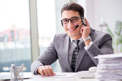 The helpdesk operator talking on phone in office. Helpdesk operator talking on phone in office stock images