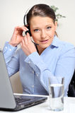 Helpdesk woman installing for work. Latin woman installing for work, adjusting her headset. Laptop open and her glass of water filled. Almost ready to go Royalty Free Stock Photos