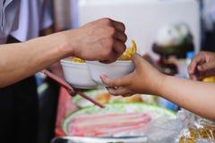 Helpend de armen in de maatschappij door voedsel te schenken: Het concept honger stock afbeeldingen