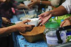 Helpend de armen in de maatschappij door voedsel te schenken: Het concept honger stock foto