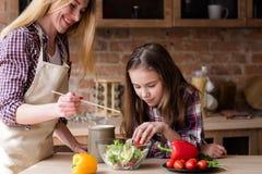 Helper girl salad dinner family cooking leisure. Moms little helper. kid girl preparing salad for dinner. happy family cooking leisure and good parenting skills royalty free stock photography