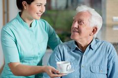 Helper giving cup of coffee. Helper giving senior men cup of coffee royalty free stock images