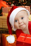 Helper with presents. Baby in Santa uniform in utter surprise, a lot of present boxes behind Royalty Free Stock Images