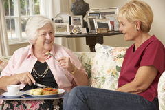 Helper Serving Senior Woman With Meal In Care Home Royalty Free Stock Photography