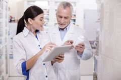 Pleasant female pharmacist consulting with colleague stock images