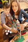 Helpful artist painting with child in the art studio Royalty Free Stock Photos
