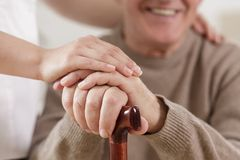 Helpful carer and happy old man. Close up of helpful carer hand and happy old man Stock Photo