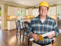 Helpful Contractor With Plans and Hard Hat Inside Custom Kitchen. Royalty Free Stock Photos
