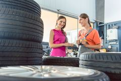 Helpful female auto mechanic checking the identification number of a tire Stock Photos