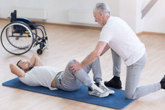 Helpful general practitioner stretching the handicapped in the sports hall Stock Photos