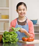Helpful girl preparing salad in kitchen Royalty Free Stock Images