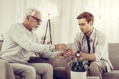 Helpful man handing the glass of water to elderly mister stock photos