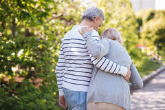 Helpful man helping senior wife in the park. Hand in hand for the whole life . Attentive caring athletic men caring about his elderly wife and helping her to Royalty Free Stock Photography