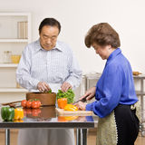 Helpful man preparing salad with wife in kitchen stock images