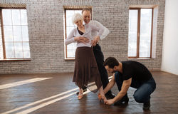 Helpful mature dance instructor teaching aged couple in the ballroom Royalty Free Stock Photo