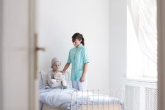 Helpful nurse comforting sick teenage patient with cancer in medical center royalty free stock images