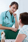 Helpful nurse. Photo of pretty helpful nurse and sick woman Royalty Free Stock Photos