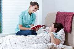Helpful nurse reading book Royalty Free Stock Photos