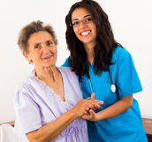 Helpful Nurses with Patients. Happy joyful nurses caring for kind elderly patients helping their days in nursing home stock photos