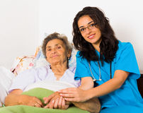 Helpful Nurses with Patients. Happy joyful nurses caring for kind elderly patients helping their days in nursing home stock images