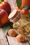 Helpful peach pits oil in a bottle close-up on the table. vertic Stock Photo