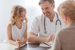 Pediatrician and sick boy in a doctor`s office stock photos