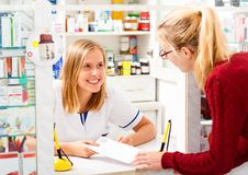 Helpful Pharmacist. Kind helpful pharmacist explaining tor patient how to take her remedy stock images