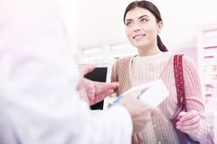 Helpful pharmacist selling a cure to a waiting customer. Pharmacist selling a cure. Helpful pharmacist selling a prescribed cure to a waiting hopeful customer stock photo