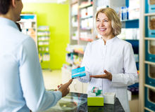 Helpful pharmacist serving and consulting man Stock Image