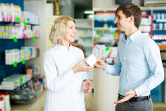 Helpful pharmacist serving and consulting man Royalty Free Stock Image