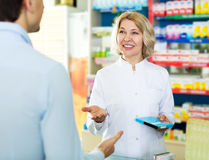 Helpful pharmacist serving and consulting man royalty free stock photography