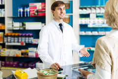 Helpful pharmacist serving young woman in pharmacy Stock Photo