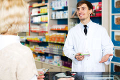 Helpful pharmacist serving young woman in pharmacy Royalty Free Stock Images
